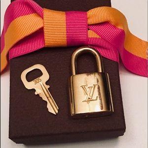 LOUIS VUITTON LOCK W/KEY, COMES W/BOX & LV RIBBON